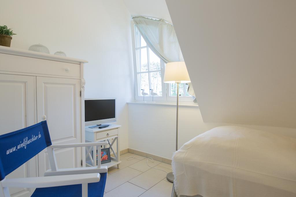 Kleines Schlafzimmer mit zwei Einzelbetten mit Blick auf den Deich und teilweise Ostsee.